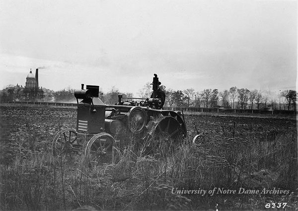 A worker on a tractor plows a Notre Dame farm field in the spring of 1924.  The Main Building and Power Plant smoke stack are in the background.