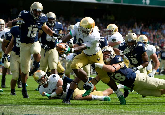 Notre Dame running back Theo Riddick rushes to the end zone for a touchdown as Navy Midshipmen linebacker Keegan Wetzel (48) attempts to tackle during the first quarter the 2012 Emerald Isle Classic at Aviva Stadium in Dublin, Ireland.