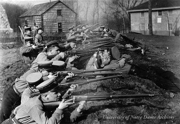 Students in the military training corps at rifle target practice in the trenches, 1915-1916.  The Founder's Monument, Log Chapel, and Old College are in the background.