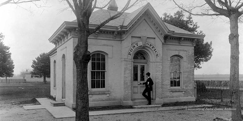 A man dropping a letter into the mail slot of the front door of Notre Dame's first Post Office built in 1856, located east of the present location of the Sorin Statue on the Main Quad, c1890s.