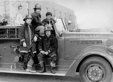 Notre Dame Fire Department firemen posed on a fire truck, c1970s.